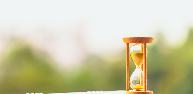 Hourglass on calendar concept for time slipping away for important appointment date.