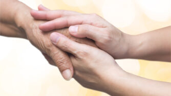 Caregiver, carer hand holding elder hand for hospice care. Philanthropy kindness to disabled old people concept with gold bokeh background.Happy mother's day.